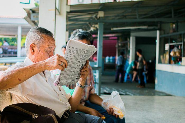 Un monsieur lit le journal en attendant la navette